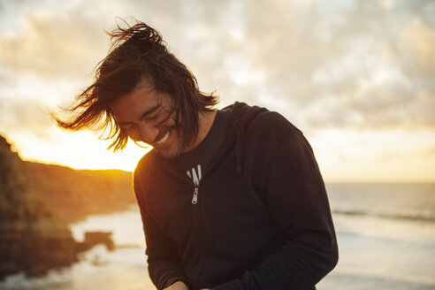 Happy man smiling while standing at beach against cloudy sky during sunset - CAVF30677