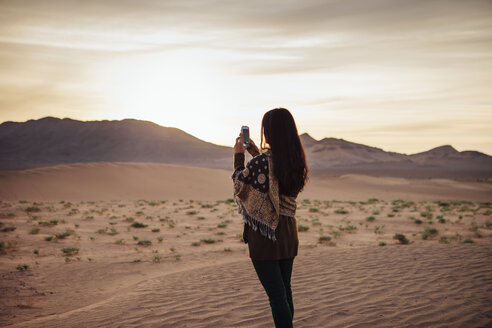 Woman photographing through mobile phone at desert against cloudy sky - CAVF30719