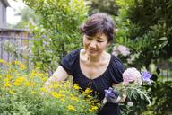 Senior woman holding flowers while gardening in backyard - CAVF30803