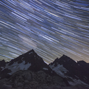 Low angle view of star trails over mountains at night - CAVF30824