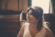 Happy bride looking away while sitting at home - CAVF30839