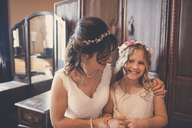 Portrait of happy flower girl with bride standing by cabinet at home - CAVF30842