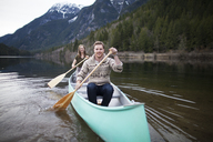 Happy young couple canoeing on lake against mountains - CAVF30869