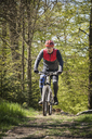 Mature man riding on mountain bike through forest - FOLF02937