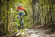 Mature man riding on mountain bike through forest - FOLF02943