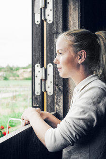 Woman leaning on stable door - FOLF03072