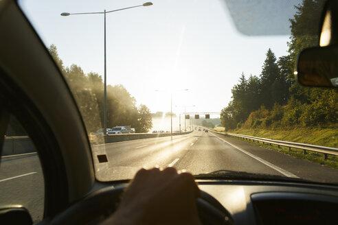 Man driving car on highway at sunset - FOLF03552