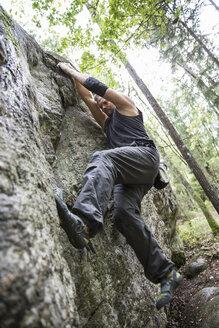 Sportsman doing bouldering in forest - FOLF03588