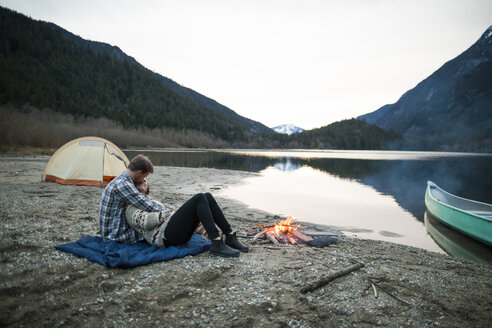 Boyfriend embracing girlfriend while sitting on picnic blanket at lakeshore by campfire against clear sky - CAVF30877