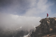 Side view of hiker standing on cliff against cloudy sky - CAVF30916