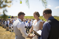 Young couple getting married by priest during sunny day - CAVF30925