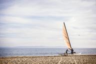 Family making sailboat at beach - CAVF31057