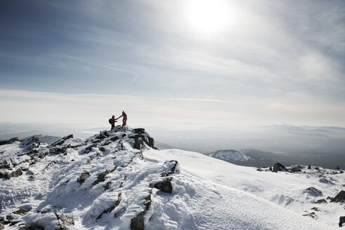 Friends hiking on snow covered mountain against sky - CAVF31111