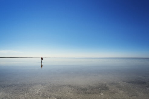 Mid distance of man standing on beach against clear blue sky - CAVF31114