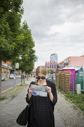 Young woman in Berlin with city map - FOLF03667