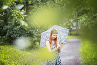 Woman wearing floral dress standing with umbrella in park - FOLF03685