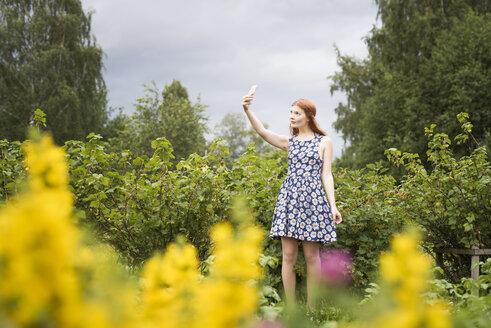 Woman taking selfie in rural scenery - FOLF03688