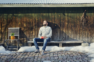 Mid adult man sitting on bench by wooden shed - FOLF03841