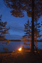 Man by bonfire on riverbank - FOLF03877