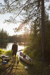 Man by canoe on riverbank - FOLF03880