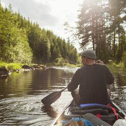 Man paddling canoe along river - FOLF03886