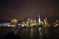 Woman´s hands photographing skyline with smart phone - FOLF04078