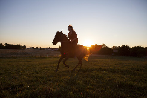 Woman horse-riding on field at sunset - FAF00083