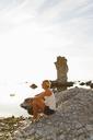 Woman sitting on rocks by sea at sunset - FOLF04162