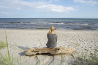 Mature woman sitting on driftwood and looking at sea - FOLF04210