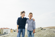 Boys standing on asphalt mound and laughing - FOLF04285