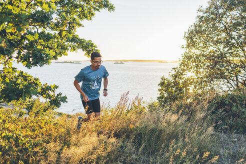 Mid adult man jogging at seashore - FOLF04294
