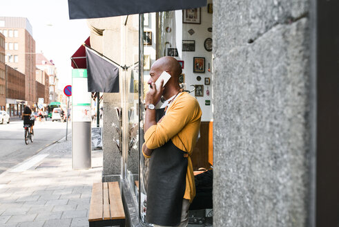 Barber standing on street and using smart phone - FOLF04513
