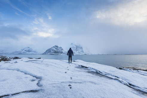 Man standing in snow looking out to sea - FOLF04762