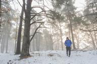 Man walking through a snowy forest - FOLF04789