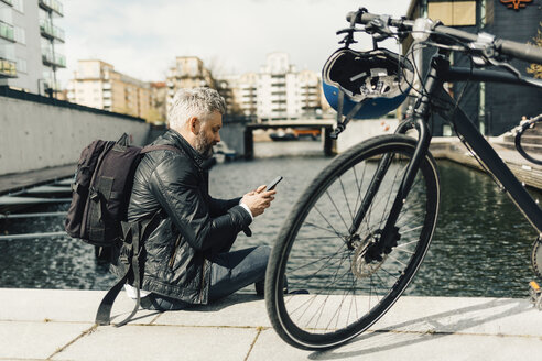 Man on smart phone with bicycle in Stockholm, Sweden - FOLF04927