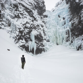 Man beside frozen waterfall in Fulufjallet National Park, Sweden - FOLF05065