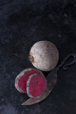 Whole and sliced beetroot and an old knife on dark metal - CSF29016