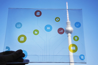 Germany, Berlin, hand holding futuristic device with digital icons in front of Tv tower - FMKF05016