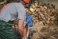 Happy father and son sawing wood together - PAF01788
