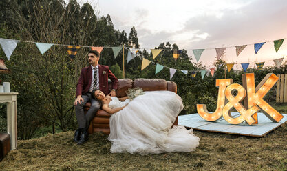 Bride lying over sofa with groom in the field - DAPF00926