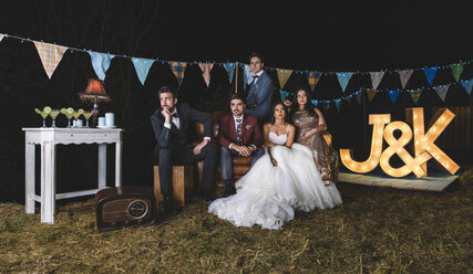 Portrait of wedding couple with friends on sofa on a night field party - DAPF00932