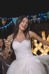 Happy bride laughing and dancing while holding cocktail on an outdoor night party - DAPF00935