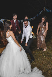 Happy bride dancing and having fun with her friends on a night field party - DAPF00941