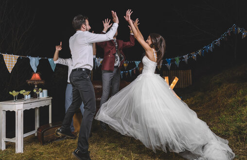 Happy bride jumping and giving high five with her friends on a night field party with friends - DAPF00944