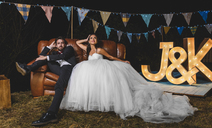 Portrait of wedding couple posing sitting on sofa on a night field party - DAPF00950