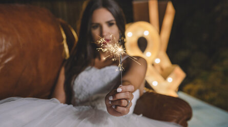 Close-up of sparkler in the hand of a bride lying on sofa on a night party outdoors - DAPF00959