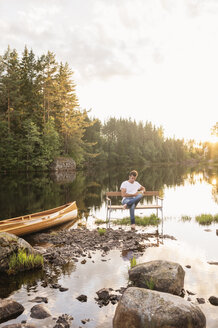 Man sitting on bench in middle of lake - FOLF05589