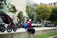 Cheerful mother playing with baby girl while sitting on retaining wall in city - CAVF31161