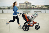 Side view of woman pushing baby stroller while jogging in city - CAVF31167