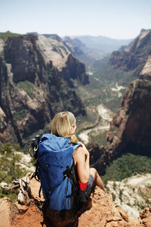 Rear view of female hiker sitting on mountain cliff - CAVF31185